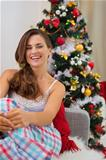 Smiling young woman in pajamas near Christmas tree