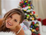 Smiling young woman in pajamas laying on couch near Christmas tree