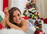 Smiling young woman in pajamas laying on sofa near Christmas tree