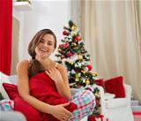 Smiling young woman in pajamas sitting on sofa near Christmas tree