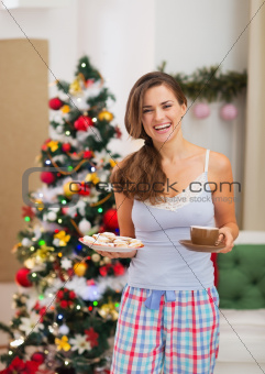 Happy young woman in pajamas with Christmas snacks near Christmas tree