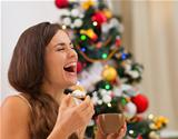Smiling young woman in pajamas eating cookies with hot chocolate near Christmas tree