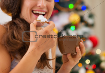Closeup on young woman eating cookies with hot chocolate near Christmas tree