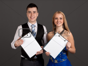 Young man and woman holding clip boards