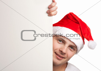 Man with santa hat peeking out of blank poster