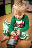 Cute Young Boy Enjoying Christmas Morning Near The Tree.