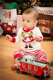 Cute Infant Mixed Race Baby Enjoying Christmas Morning Near The Tree.