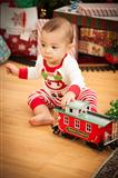 Cute Infant Mixed Race Baby Enjoying Christmas Morning Near The Tree.