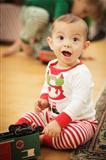 Cute Infant Baby Enjoying Christmas Morning Near The Tree.