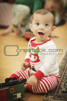 Cute Infant Baby Enjoying Christmas Morning Near The Tree.
