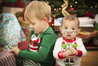 Cute Infant Baby and Young Boy Enjoying Christmas Morning Near The Tree.