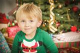 Cute Young Boy Enjoying Christmas Morning Near The Tree.