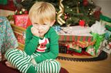 Grumpy Cute Young Boy on Christmas Morning Near The Tree.