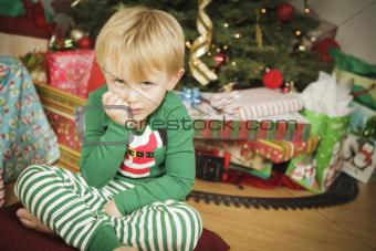 Grumpy Cute Young Boy on Christmas Morning Near The Tree.