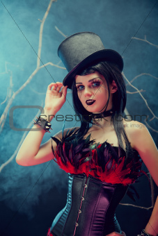 Attractive smiling gothic girl in tophat and feather corset