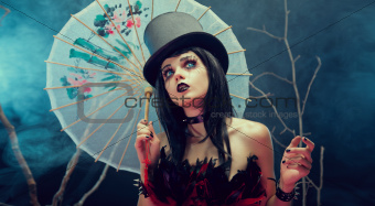 Attractive gothic girl in top hat with Chinese umbrella looking