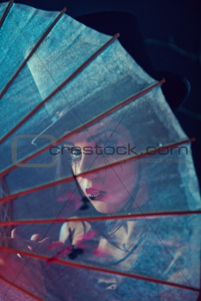 Attractive gothic lady in top hat looking through Chinese umbrel