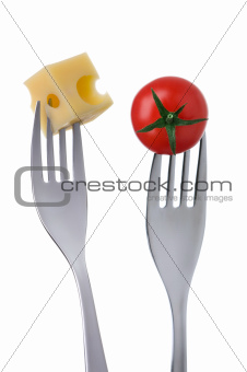 tomato and cheese on forks against white