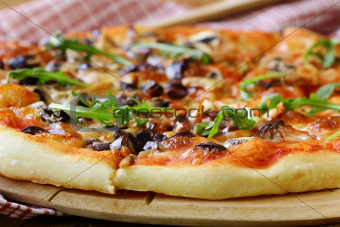 Italian pizza with mushrooms and olives on a wooden board