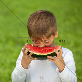 Little boy eating a fresh watermelon
