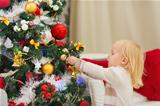Baby girl decorating Christmas tree