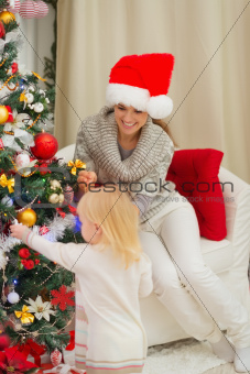 Mother looking on baby decorating Christmas tree