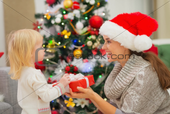 Baby girl presenting mother Christmas gift