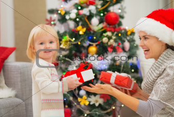 Mother and baby girl changing Christmas presents