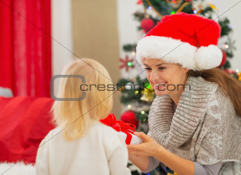 Mother presenting baby girl Christmas present