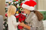 Mother and baby girl with Christmas rose near Christmas tree