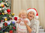Portrait of happy mother and baby near Christmas tree