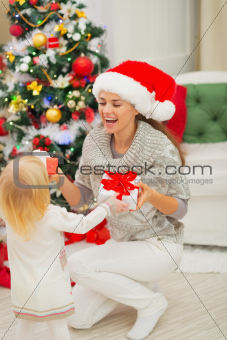 Mom and baby girl changing Christmas presents