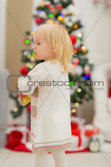 Baby in front of Christmas tree. Rear view