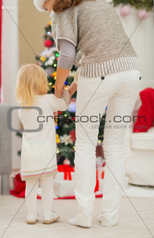Baby and mother in front of Christmas tree. Rear view