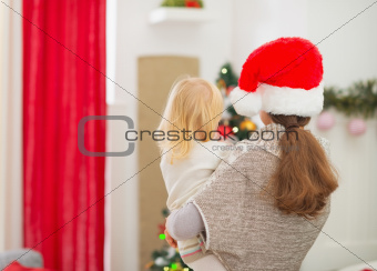 Mother holding baby and looking on Christmas tree. Rear view