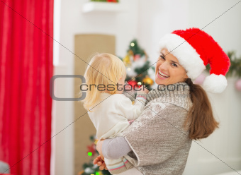 Mother holding baby in front of Christmas tree