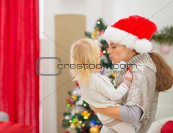 Mother kissing baby in front of Christmas tree