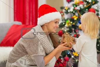 Happy mother and baby playing near Christmas tree