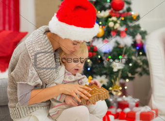 Young mom and baby girl playing near Christmas tree