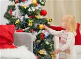 Baby touching Christmas ball on Christmas tree