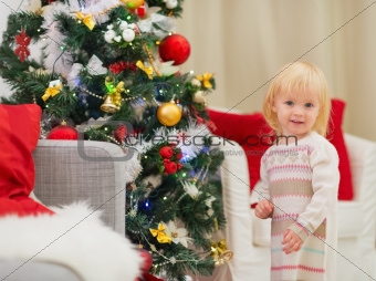Portrait of baby girl near Christmas tree