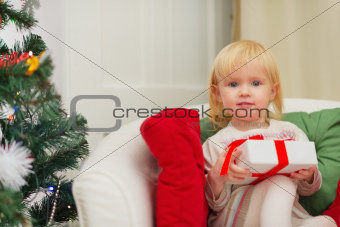 Portrait of baby sitting on chair with Christmas present box