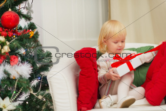 Baby sitting on chair and open Christmas present box