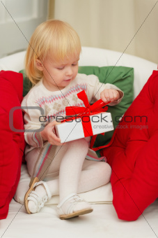 Baby sitting on chair and open Christmas gift box