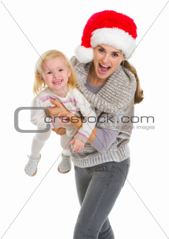 Christmas portrait of smiling mother playing with baby girl