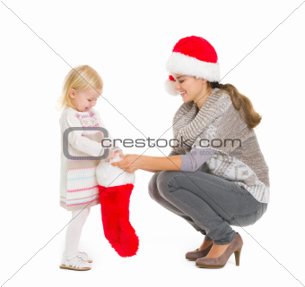 Baby girl taking out present from Christmas sock