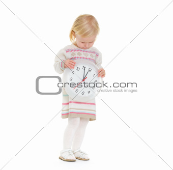 Christmas portrait of baby girl looking on clock