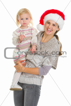 Christmas portrait of happy mother and eating cookie baby girl