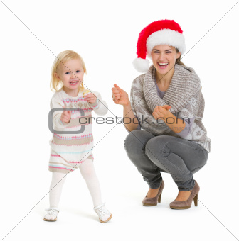 Christmas portrait of happy mother and baby girl dancing