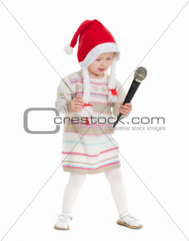 Baby girl in Christmas hat dancing with microphone